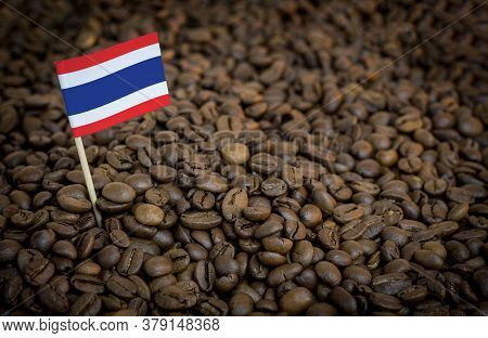Thailand Flag Sticking In Roasted Coffee Beans. The Concept Of Export And Import Of Coffee