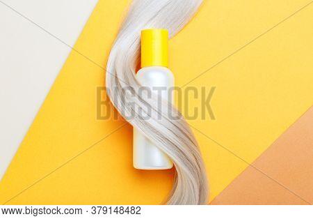 Shampoo Bottle Mockup Strand In Lock Curl Of Blonde Hair On Orange Color Background. Yellow Bottle S