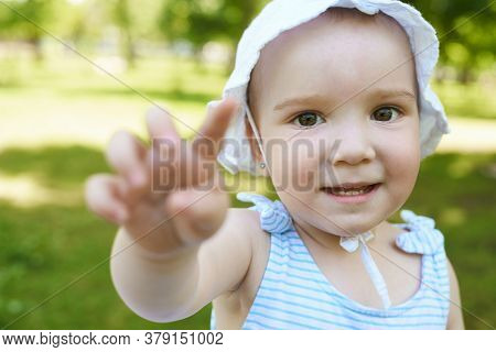 A Baby Is Pointing To The Camera. A Little Girl Is Looking Into Camera In The Park.
