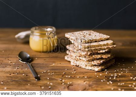 Stack Of Crusty Crispbread On A Brown Wooden Background In Close Up. Delicious Substitute For Bread.