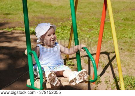 A Baby Rides On A Swing. A Baby Have A Fun On A Flip-flap In The Park.