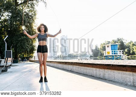 An Attractive African-american Woman Is Jumping With A Skipping Rope On The City Waterfront With An