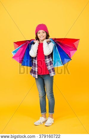 Shop Whatever You Want. Happy Girl Hold Shopping Bags. Little Shopper Yellow Background. Kids Shop.