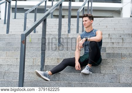 Portrait Of A Confident Sporty Man. Young Sportsman Sitting Outdoors After Good Jogging Workout. You