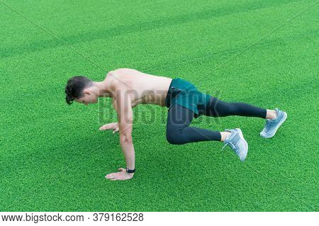 Athletic Man Doing Running Plank Exercise. Muscular Sportsman Training In Green Grass. Run As You Br