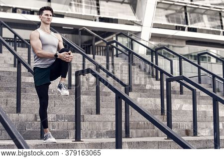 Portrait Of An Athletic Sportsman In Jogging Sportswear. Young Fitness Man Runner Stretching Legs Be