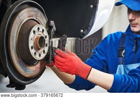Automobile brake pads replacement in car repair shop or garage