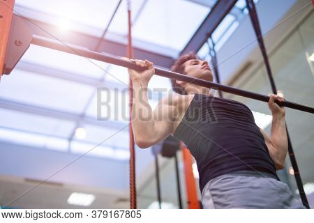 Man doing free body calisthenic pull-ups to traing his back and shoudlers in a gym, fitness and bodybuilding concept