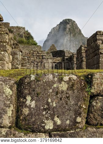 Misty Peak Of Huayna Picchu In The Distance With Stone Wall In The Foreground