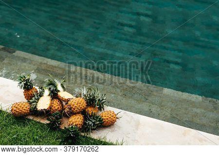 Healthy Raw Organic Food. Fresh Ripe Pineapples Near Pure Water In Swimming Pool. Juicy Fruit. Veget