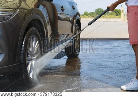 Close Up Of A Man Holding A High Pressure Water Spray Wand Washing The Front Wheel Of A Car On An Ou