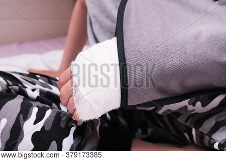 A Child Broken Arm In Plaster Case And Textile Fixing Bandage, Hand Injury Because Of Accident, Fore