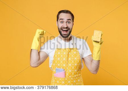 Excited Young Man Househusband In Apron Rubber Gloves Hold Cleaning Sponge Rag While Doing Housework