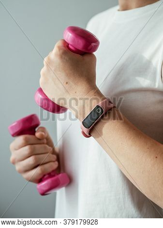Unrecognizable Young Woman In White Shirt With Pink Wearable Device And Bright Pink Colored Dumb-bel