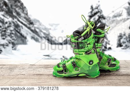 Ski Boots On A Wooden Table Against The Background Of Mountains. Bright Green Sports Ski Boots. Alpi