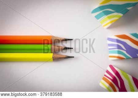 Colorful Erasers And Simple Pencils On A Light Background. Close Up. Selective Focus