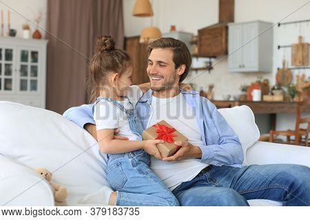 Cute Kid Daughter Make Surprise To Daddy, Little Girl Presents Gift Box To Father Sit On Sofa. Fathe