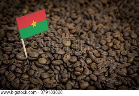 Burkina Faso Flag Sticking In Roasted Coffee Beans. The Concept Of Export And Import Of Coffee