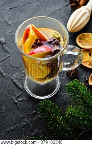 Hot Christmas Mulled Wine Or Gluhwein With Spices And Ingredients On Black Background. Traditional D