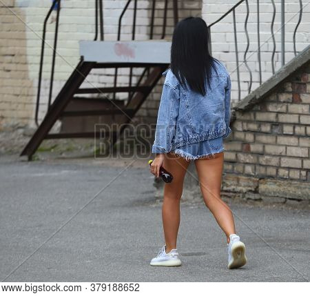 Dark-haired Girl In A Denim Jacket And Short Denim Shorts, Prospekt Bolshevikov, Saint Petersburg, R