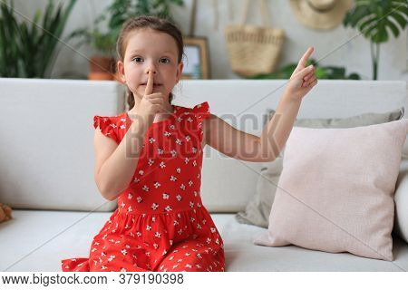 Little Girl Child Keeping Finger On Her Lips And Asking To Keep Quiet.