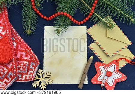 Old Paper Sheet With Post Envelope, Knitted Mittens And Evergreen Conifer On Table. Wish Letter To S