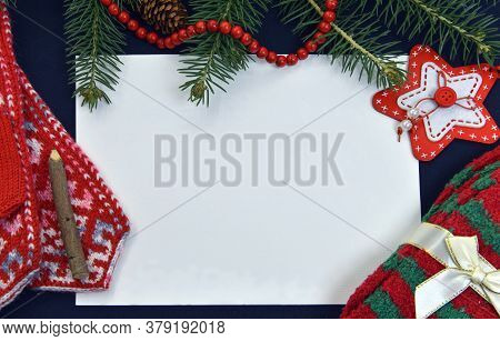 Empty Paper With Knitted Mittens And Socks On Table With Conifer. Christmas And New Year Background