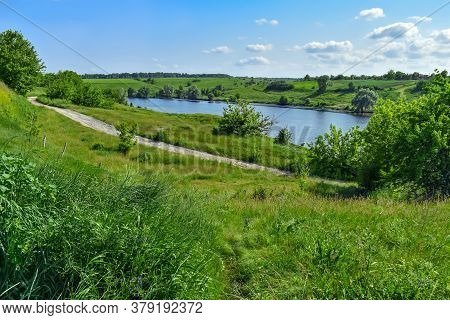 Dirt Road Among Green Hills On The Shore Of A Pond With Blue Water. Bright Natural Panorama With A L
