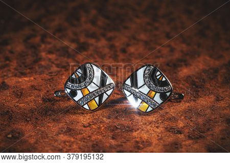 Pair Of Beautiful Earrings On A Brown Background