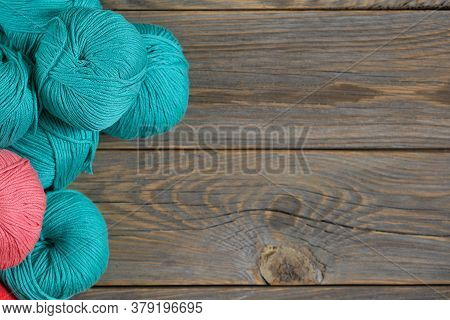 Balls Of Bright Woolen Yarn On Old Wood Background. With Copy Space