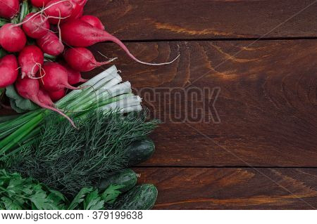 Vegetables, Radishes, Cucumbers And A Bunch Of Green Onions And Dill On A Brown Wooden Background To