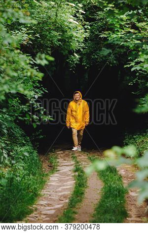 Traveler Man In Yellow Raincoat Hiking By Rainy Forest
