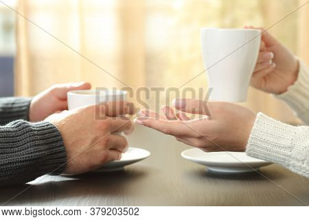 Close Up Of A Couple Hands Talking Holding Coffee Cups Sitting On A Table Next To The Window At Home