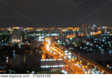 Bokeh Abstract Background Of Street Road With Skyscraper Buildings In Bangkok City, Thailand With Li