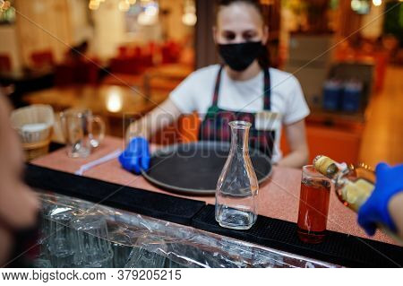 Waiter In Protective Mask Hold Tray With Alcohol Drink In The Restaurant.
