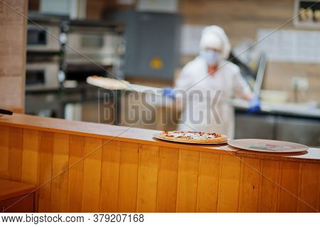 Pizza Maker In Protective Mask Working In The Pizzeria.
