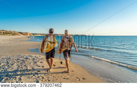 Two Senior Surfers With Surfboard Having Fun On Empty Remote Beach Enjoying Retirement Lifestyle