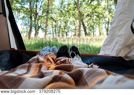 Two People Lie In A Tourist Tent, Inside View. Feet Under The Covers In The Tent. Tourist Camp
