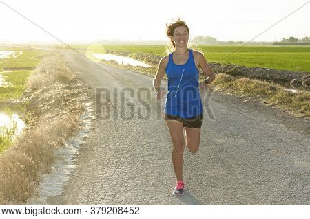 A Sportswoman With Blue Shirt Running Down A Path Next To A Rice Field At Backlight Of Sunset Or Sun