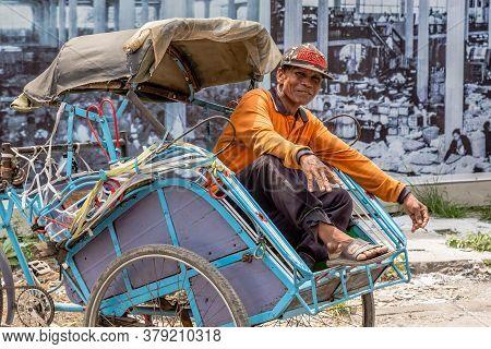 Semarang, Indonesia - November, 01, 2017: Taxi Driver Waiting In His Own Bicyle Taxi In Semarang, In