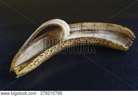 Discarded Banana Peel On Black Background. Overripe Banana Peel With Brown Spots. Food Waste. Close-