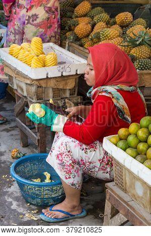 Surabaya, Indonesia - November, 05, 2017: Woman Cutting Pineapple At The Market In Surabaya In Indon