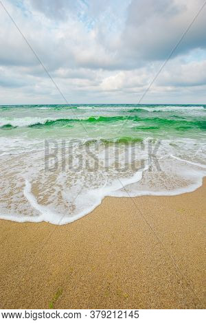 Green Sea Waves Beneath A Grey Sky. Tide Rolling On The Beach. Empty Calm Scenery. Loneliness Concep