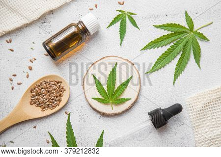Flat Lay Composition Top View. Marijuana Leaves, Cannabis Oil And Hemp Seeds. Glass Bottle With Cbd