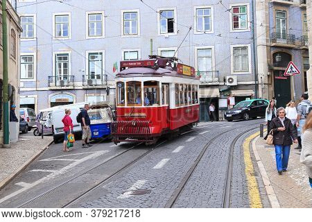 Lisbon, Portugal - June 4, 2018: People Ride The Red Tram Tour In Alfama District, Lisbon, Portugal.
