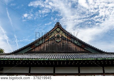 Wooden, Richly Decorated Nijo Castle Roof In Kyoto, With Golden Ornaments, Japan. Blue Sky In The Ba