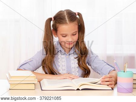 Education And School Concept. Child Is Sitting At The Desk And Reading A Book. Cute Little Student G