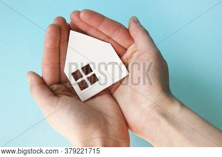 Hands Holding White Paper House, Family Home, Homeless Housing And Home Protecting Insurance Concept