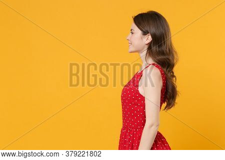 Side View Of Smiling Young Brunette Woman Girl In Red Summer Dress Posing Isolated On Yellow Backgro