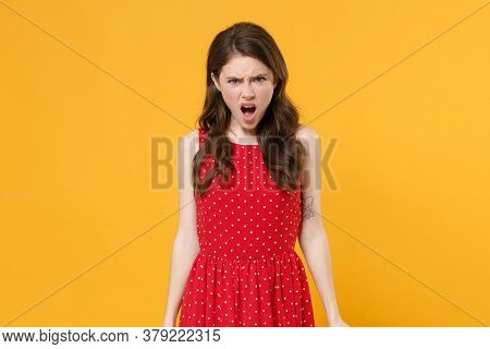 Dissatisfied Irritated Young Brunette Woman Girl In Red Summer Dress Posing Isolated On Yellow Wall